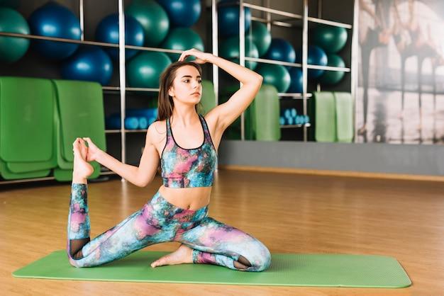 Pięknej kobiety ćwiczy joga na macie przy gym Darmowe Zdjęcia