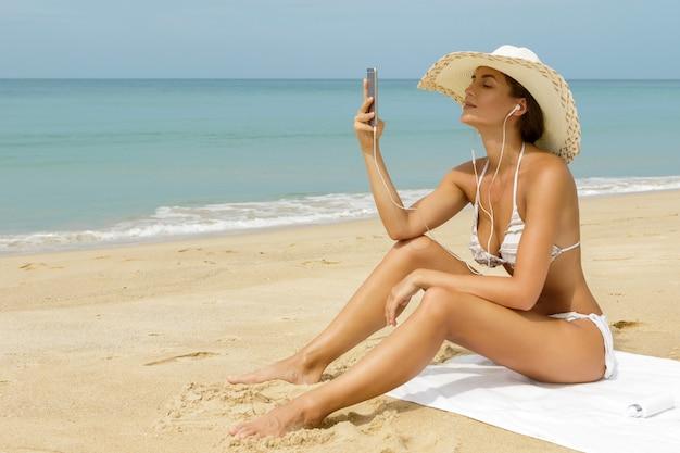Pięknej Kobiety Słuchająca Muzyka Na Plaży Premium Zdjęcia