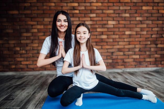 Pięknej matki i córki uprawiającej gimnastykę i rozciągającą się w domu. zdrowy styl życia rodziny. Premium Zdjęcia
