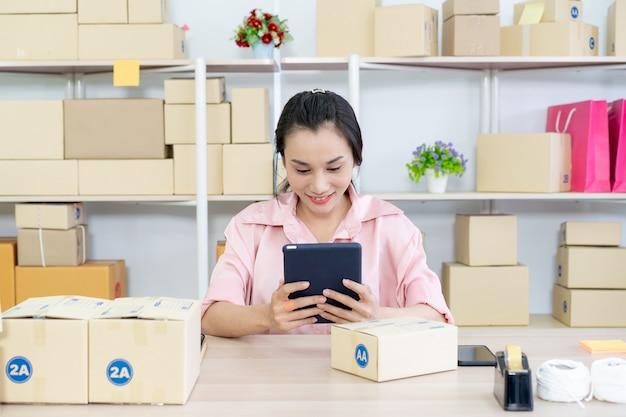 Pięknej Młodej Azjatyckiej Kobiety Sprzedawca Online Pakuje I Sprawdza Dla Przychodzących Zamówień W Magazynie Premium Zdjęcia
