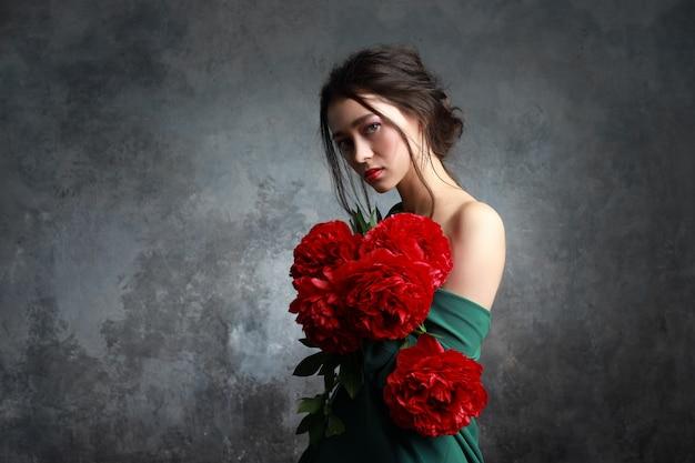 Pięknej Młodej Europejskiej Dziewczyny Przyglądający Azjata Z Peon Kwiatami Premium Zdjęcia