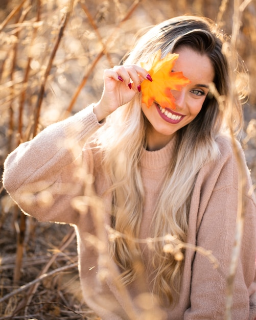 Pięknej młodej kobiety podmuchowi liście klonowi patrzeje kamerę Darmowe Zdjęcia