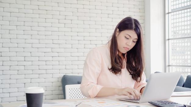 Pięknej młodej uśmiechniętej azjatykciej kobiety pracujący laptop na biurku w żywym pokoju w domu. Darmowe Zdjęcia