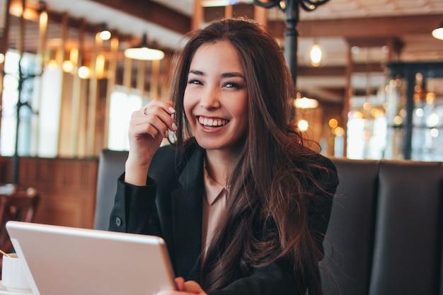 Pięknej Powabnej Brunetki Szczęśliwa Azjatykcia Dziewczyna Z Pastylką Przy Stołem W Kawiarni Premium Zdjęcia