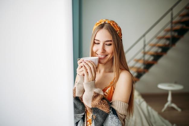 Pięknej Uśmiechniętej Młodej Kobiety Uczciwa Długie Włosy Dziewczyna Jest Ubranym W Wygodnym Trykotowym Kardiganie Z Filiżanką Herbaty Blisko Okno W Domu Premium Zdjęcia