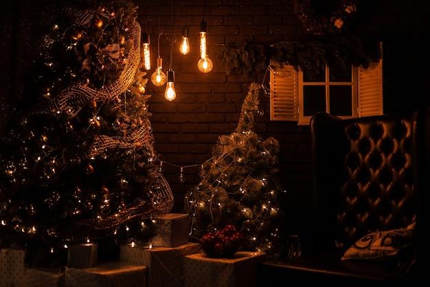 Pięknie Udekorowany Salon Z Choinką Ze Skórzanym Fotelem Vintage Ze Starymi żółtymi Lampkami Z Prezentami Bożonarodzeniowymi I Zabawkami Wieczorem. Premium Zdjęcia