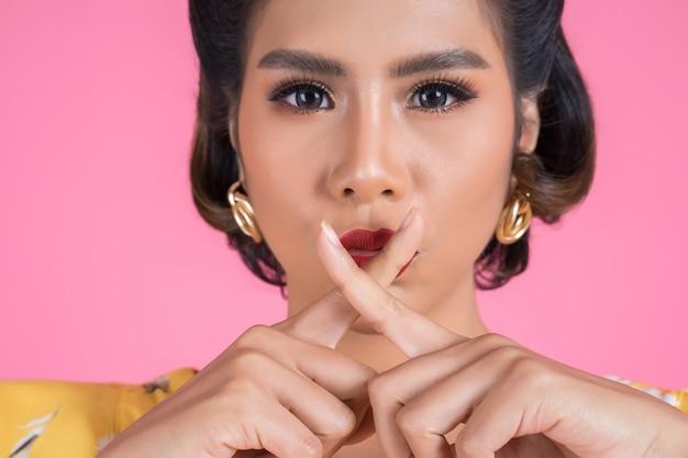 Piękno azjatykciej kobiety czerwone wargi i palec pokazuje ucichnięcie ciszy znaka Darmowe Zdjęcia