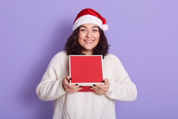 Piękno Boże Narodzenie Dziewczyna Modelka Trzyma Czerwone Pudełko, Patrząc Bezpośrednio, Ma Ciemne Faliste Włosy I Piękny Manicure, Dziewczyna Ubrana W Biały Sweter Z Dzianiny I Czapkę Mikołaja. Premium Zdjęcia