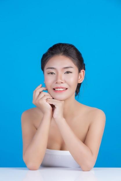 Piękno kobiet z doskonałymi obrazami zdrowia skóry dotykając jej twarzy i uśmiechając się jak spa, rozpieszczamy jej skórę niebiesko Darmowe Zdjęcia