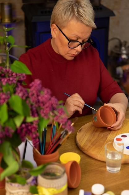 Piękny Artysta Maluje Kwiaty Bzu Na Glinianym Garnku W Obszarze Roboczym Wiosna Stylu życia Premium Zdjęcia