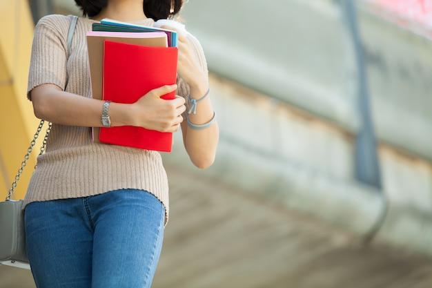 Piękny azjatycki żeński student collegu trzyma jej książki i filiżankę kawy Premium Zdjęcia