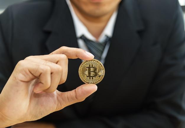 Piękny Biznesowy Mężczyzna Model Trzyma Bitcoin Złocistą Monetę. Crypto Mining Farm. Handlowcy I Giełdy, Premium Zdjęcia