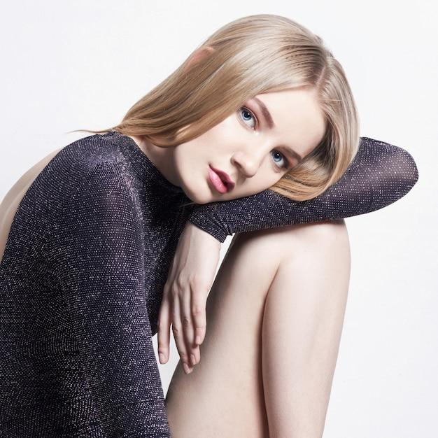 Piękny blond kobiety obsiadanie na stolec. Premium Zdjęcia