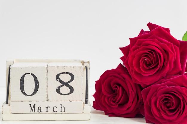 Piękny bukiet czerwonych róż i drewniany sześcian kalendarz na drewnianym tle. koncepcja gratulacji 8 marca lub dnia woomana. Premium Zdjęcia