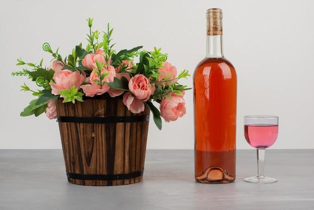 Piękny Bukiet Kwiatów I Butelka Różowego Wina Na Szarym Stole Darmowe Zdjęcia