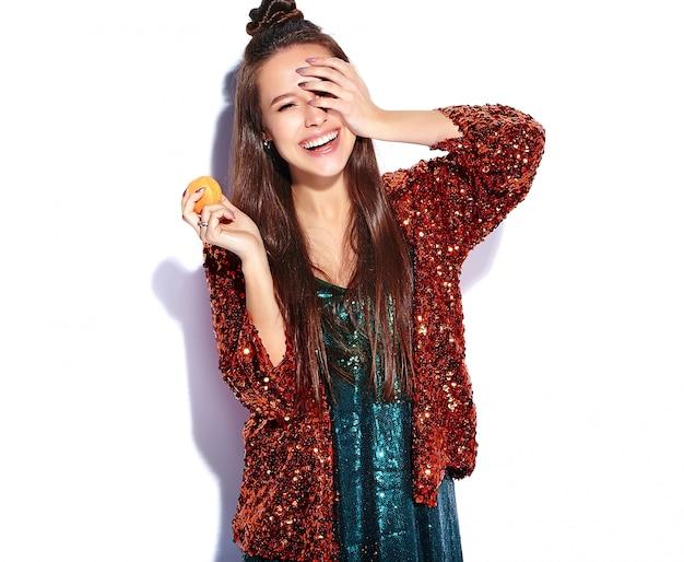 Piękny Caucasian Uśmiechnięty Modniś Brunetki Kobiety Model W Jaskrawym Shinny Odbija Lato Eleganckiej Kurtce I Zieleni Sukni Odizolowywających. Jedzenie Francuskiego Makaronika Darmowe Zdjęcia