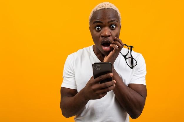 Piękny Czarny Amerykański Uczeń Z Białych Włosów Spojrzeniami W Niespodziance Na Telefonie Na żółtym Pracownianym Tle Premium Zdjęcia