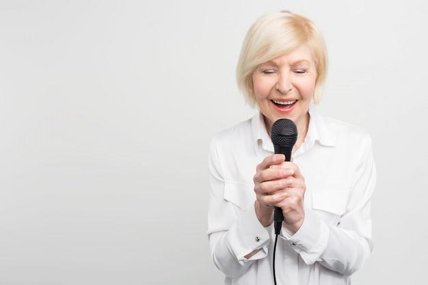 Piękny I Delikatny Obraz Niesamowitej Dojrzałej Kobiety śpiewającej Piosenkę Z Zamkniętymi Oczami Za Pomocą Mikrofonu. Premium Zdjęcia