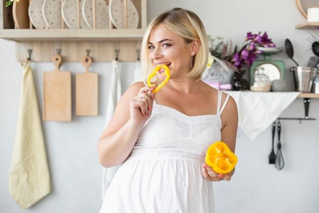 Piękny Kobieta W Ciąży Je żółtego Pieprzu Darmowe Zdjęcia