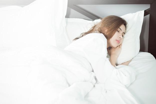 Piękny kobiety dosypianie na łóżku Premium Zdjęcia