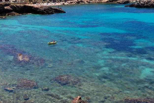 Piękny Krajobraz Na Ibizie Błękitnego Oceanu W Słoneczny Dzień Z Mężczyzną Uprawiającym Wiosło Surfowania. Koncepcja Lato I Wakacje. Premium Zdjęcia