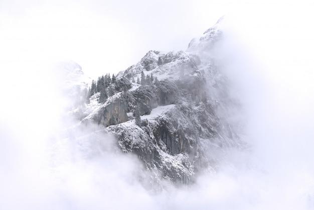 Piękny Krajobraz Zaśnieżonych Gór I Mgły Między Szczytami. Premium Zdjęcia