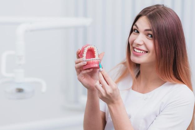 Piękny lekarz ortodonta pokazuje, jak dbać o zęby Premium Zdjęcia