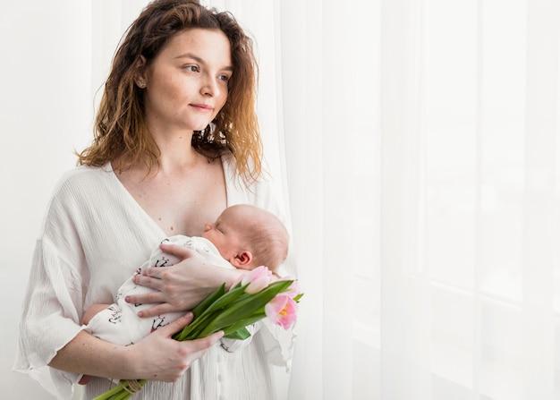 Piękny macierzysty patrzeć oddalony podczas gdy niosący jej dziecka stoi blisko białej zasłony Darmowe Zdjęcia