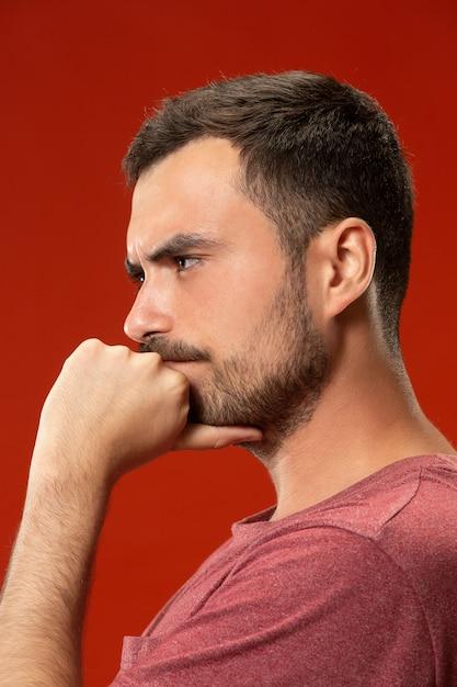 Piękny Mężczyzna Patrzeje Zaskakujący I Oszołomiony Odosobnionym Na Czerwieni Darmowe Zdjęcia