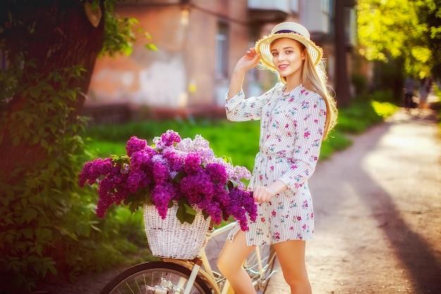 Piękny młody nastolatek z rocznika bicyklem i kwiaty na mieście w świetle słonecznym plenerowym. Premium Zdjęcia