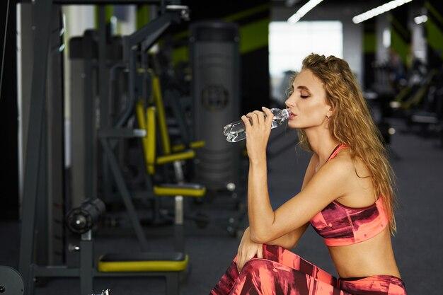 Piękny młody sporty kobiety obsiadanie na ćwiczenie maszynie w gym. przerwa po ciężkim treningu. Premium Zdjęcia