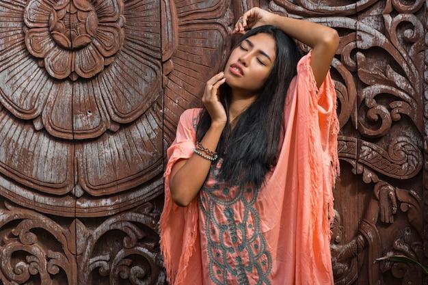 Piękny Model Azjatycki W Różowej Sukience Boho Pozuje Na Drewnianej ścianie Ozdobnej. Darmowe Zdjęcia