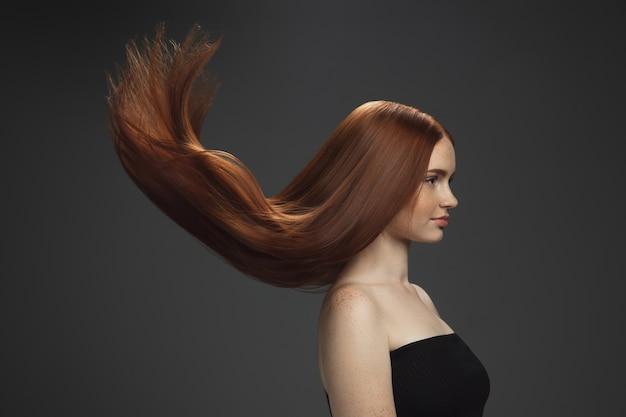 Piękny Model Z Długimi, Gładkimi, Rozwianymi Rudymi Włosami Odizolowanymi Na Ciemno Darmowe Zdjęcia