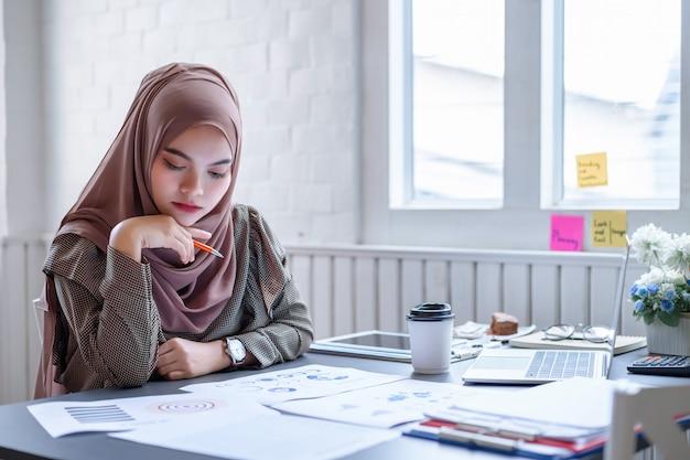 Piękny Nowożytny Arabski Biznesowej Kobiety Brązu Hidżab Dyskutuje Dane Planowania Finansowego W Kreatywnie Miejscu Pracy. Premium Zdjęcia