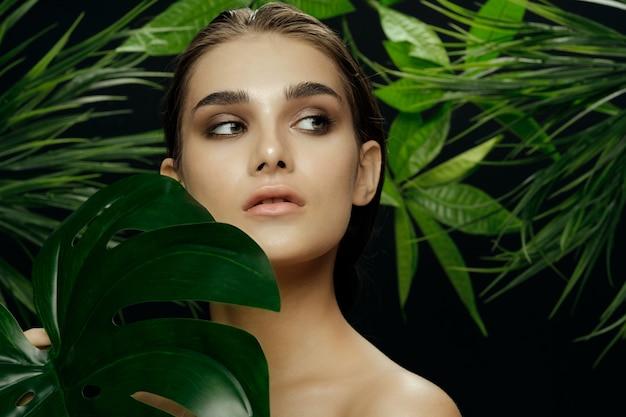 Piękny Portret Kobiety W Krzakach Palmowych, Piękna Skóra Twarzy Premium Zdjęcia
