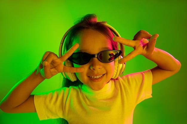 Piękny Portret Kobiety W Połowie Długości Na Białym Tle Na Zielonej ścianie W świetle Neonu. Młoda Emocjonalna Dziewczyna Nastolatka W Okulary Przeciwsłoneczne. Ludzkie Emocje, Koncepcja Wyrazu Twarzy. Modne Kolory. Taniec, Uśmiech. Darmowe Zdjęcia