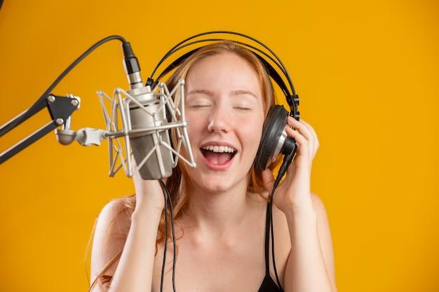 Piękny Rudzielec Kobiety Twarzy śpiew Z Kondensatorowego Srebnego Mikrofonu Otwartym Usta Spełniania Piosenki Pozą Nad Kolor żółty ściany Kopii Przestrzenią Dla Twój Teksta. Spiker Radiowy Fm. Premium Zdjęcia
