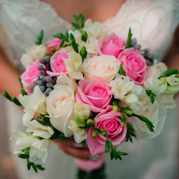 Piękny ślubny bukiet z delikatnymi białymi i różowymi różami w rękach Premium Zdjęcia