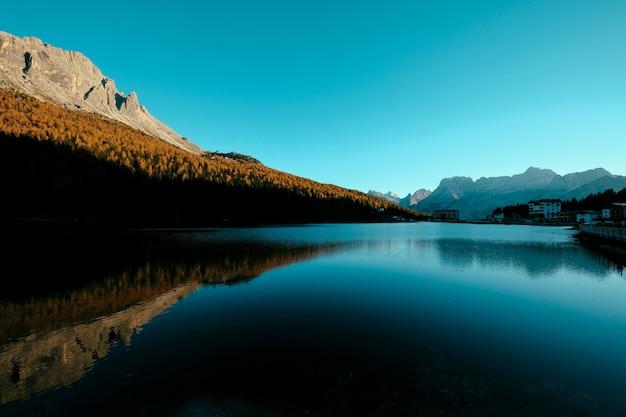 Piękny Strzał Jezioro Po środku żółtych Drzew Na Wzgórzu I Budynku Na Brzeg Darmowe Zdjęcia