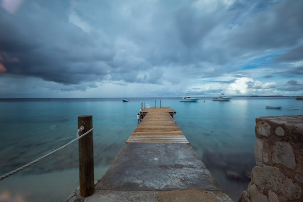 Piękny Strzał Molo Prowadzi Ocean Pod Ponurym Niebem W Bonaire, Karaiby Darmowe Zdjęcia