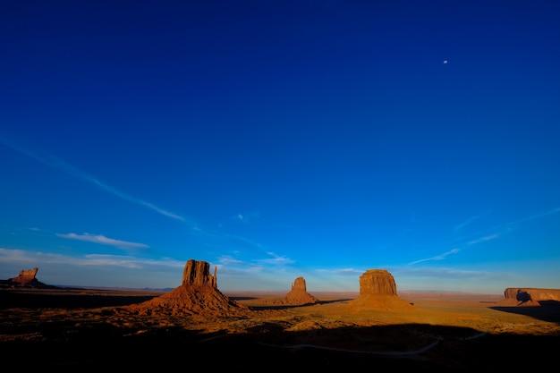 Piękny Strzał Z Drogi Pośrodku Pustyni Z Dużymi Klifami W Oddali Darmowe Zdjęcia