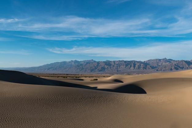 Piękny Strzał Z Pustyni Ze Szlakami Na Piasku I Skalistych Wzgórzach Pod Spokojnym Niebem Darmowe Zdjęcia