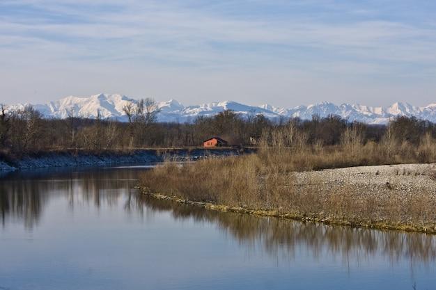 Piękny Strzał Z Rzeki Pośrodku Brzegów I Bezlistnych Drzew Z Domem W Oddali Darmowe Zdjęcia