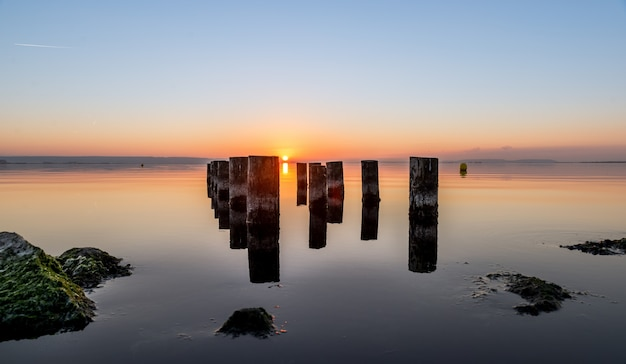 Piękny Strzał Zużyte Filary Molo Na Zbiorniku Wodnym Podczas Zachodu Słońca. Idealny Na Tapetę Darmowe Zdjęcia