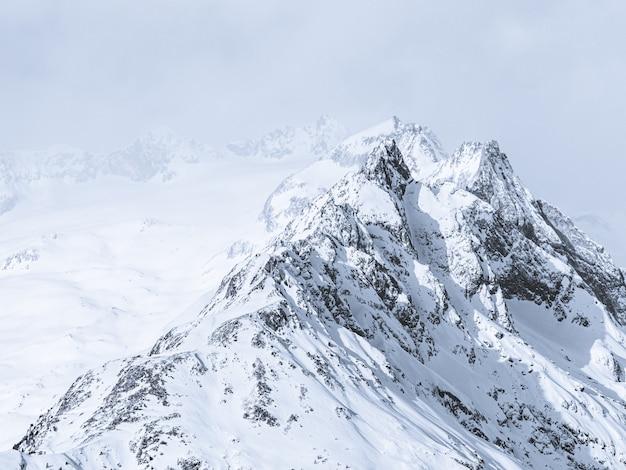 Piękny Szeroki Strzał W Góry Pokryte śniegiem Pod Mglistym Niebem Darmowe Zdjęcia