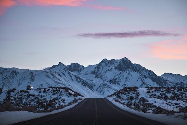 Piękny Szeroki Strzał Z Drogi W Pobliżu Gór Wypełnionych śniegiem Pod Różowym I Fioletowym Niebem Darmowe Zdjęcia