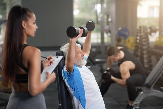 Piękny trener obserwujący starszego mężczyzna robi ćwiczeniom. Premium Zdjęcia