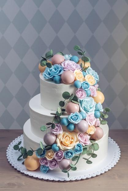 Piękny Trójpoziomowy Biały Tort Weselny Ozdobiony Kolorowymi Kwiatami Róż Premium Zdjęcia