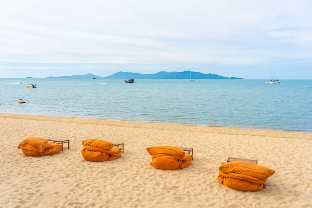 Piękny Tropikalny Plażowy Morze, Ocean Z Kokosowym Drzewkiem Palmowym, Parasol I Krzesło Na Niebieskim Niebie I Biel Chmurze Darmowe Zdjęcia