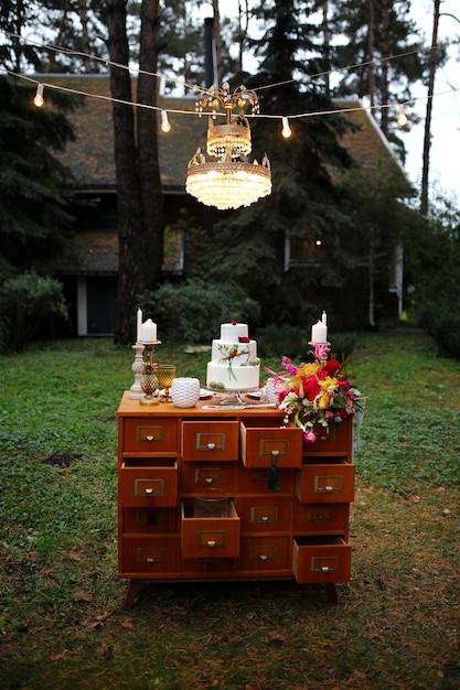 Piękny Trzypoziomowy Tort Weselny Ozdobiony Ptakiem, Różowymi Kwiatami I Gałęziami Z Zielonymi Liśćmi W Rustykalnym Stylu. świąteczny Deser. Koncepcja ślubu. Premium Zdjęcia